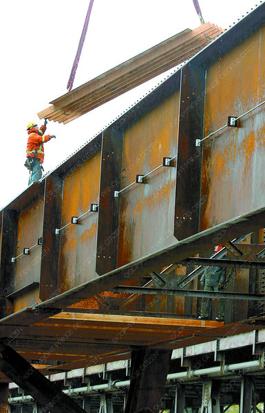 Citizen photo by David Mah Euclid Tomlinson, left, and Ryan Beers, of Surespan Construction place flooring in preparation for deck slabs on the twinning of the Simon Fraser Bridge project.