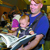 Citizen photo by David Mah Jeff Raymer, and his son Ridge, 4 months found interesting books to buy at the Mennonite Fall Fair at the Civic Centre Saturday. The Civic Centre was full of eager shoppers.