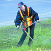 Citizen photo by Brent Braaten Terra Underwood with DART team cuts down the weeds along Highway 97 South by the Simon Fraser Bridge Monday morning.