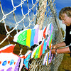 Citizen photo by Brent Braaten Maureen LeBourdais, Stream of Dreams BC north team leader, mounts the fish along a fence at Massey Drive and Carney Street that were painted by children at BC Rivers Day. There over 100 fish added this year. Stream of Dreams uses community art for watershed education.