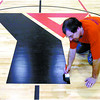 Citizen photo by David Mah John Schmidt, with Centaur Products finishes the YMCA logo on the new gym floor of the Y. The previous floor was wrecked by water damage.