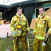 Citizen photo by David Mah Firefighters-in-training Derek Church, left, and Colin Whiteley, from Fire Etc. in Vermilion, Alberta, are learning about fire fighting in Prince George. Here, they stand in front of a burnt house on Lansdowne Road.