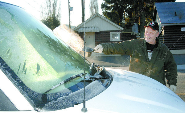 Citizen photo by Brent Braaten Chuck O'Brien uses some hot water to clear the ice off his windshield Tuesday morning on 17th Avenue. Easier than scrapping and you don't have to run your vehicle as long to get a clear windshield.