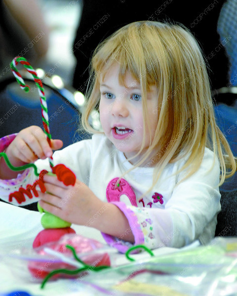 Citizen photo by Brent Braaten Hailey Goyer, 4, makes a decoration out of play dough at the Prince George Child Care Association santa Breakfast at the Salvation Army Thursday morning. 125 children attended the event that included a breakfast and visit from Santa. The group also donated over 500lbs of infant and toddler food and items to the Salvation Army to put in the hampers.