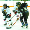 Citizen photo by David Mah Prince George PeeWee Couger Haley Reich, left, and Kallie Graham, from Grand Prairie, jostle for the puck in Friday morning's game.