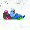 Citizen photo by Chuck Nisbett Aislynn, 3, and Eara Russell, 5, veered a little off course and came to an abrupt stop while navigating the slope at Carney Hill Monday.  It was Aislynn's first time sliding down the slope with her sister and she wasn't too impressed with her riving skills.