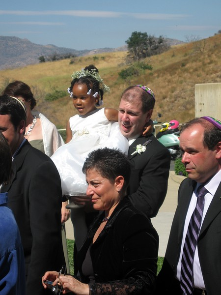 David (brother of the groom) holds daughter Shira (flower girl) while Jamie (aunt of the bride) and Gary (father of the bride) watch