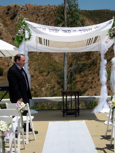 Gary (father of the bride) checks the chuppah during rehearsal.   The final chuppah included a wooden arch (not pictured here), which Gary constructed from a peach tree planted by Avram's father when he was born.