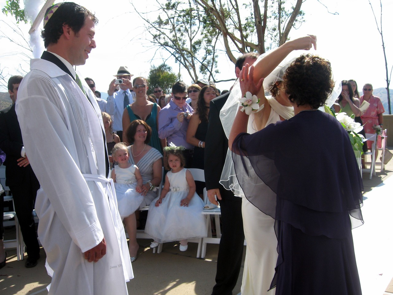 Hope (mother of the bride) kisses Abby while Avram and Gary (father of the bride) look on