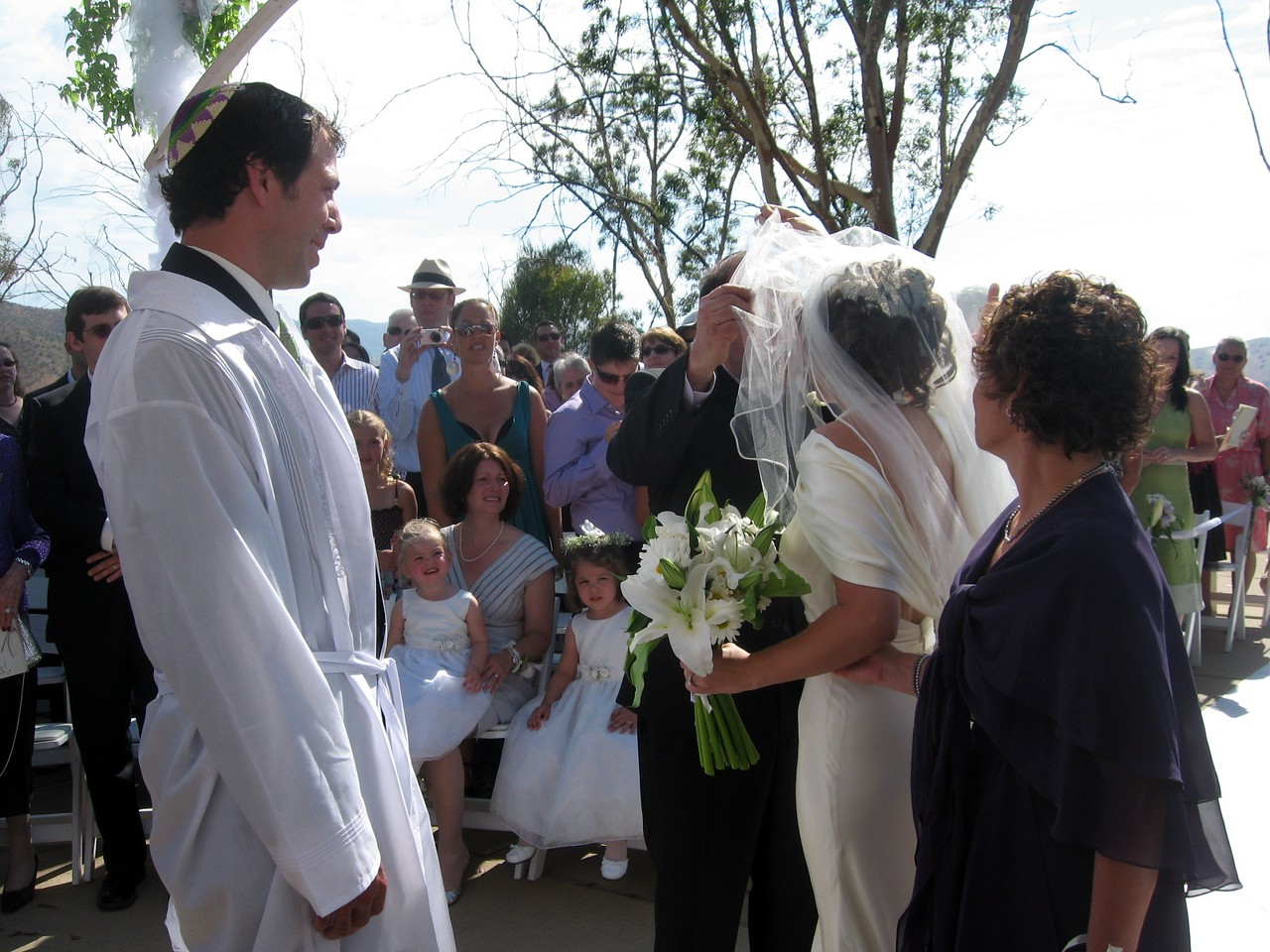 Gary (father of the bride) kisses Abby while Avram and Hope (mother of the bride) look on