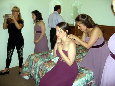 Bridesmaid Sarah helps bridesmaid Rebecca with her necklace while Gary (father of the bride) adjusts his tie