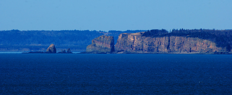 Cape Split from Baxters Harbour<br /> <br /> The cliffs are approx 90m/200ft straight down.  There is a 16km return hike from Scot's Bay to the edge of the cliffs.  From these cliffs, I've read that you can hear the tides rushing in at 13 knots (15mph/20kph) or more, causing rip tides to appear.  Mathematicians calculated that 14 billion tons of water flow past the split twice a day.  At peak times, these channels see flows that  equal all the combined flows of all the rivers and streams on Earth! Its amazing to see how fast the water levels rise.<br /> <br /> <br /> The split also marks the start of North mountain range which forms the Blomidon cliffs that have a nearly vertical drop of 290m/600ft straight to the water.  Some people actually try to scale the Blomidon cliffs.