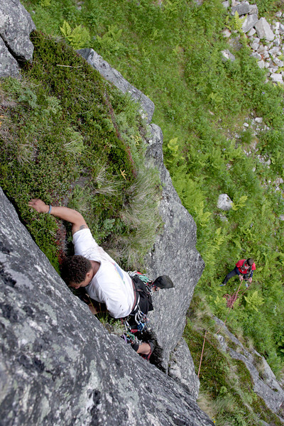 Kelsey crawls up a grassy ledge on a less frequently climbed route with Richard maintaining a belay below.
