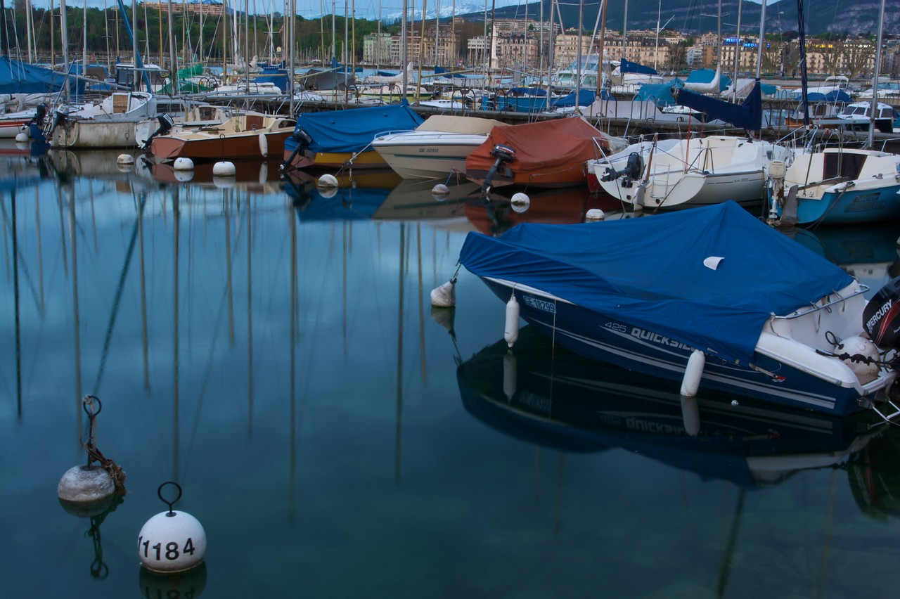 Glassy stillness • Private boats moored on Lake Geneva in the early dusk light. On the opposite shore of the lake you can see the buildings of the rive gauche; in the distance are the still-snow-covered French Alps.