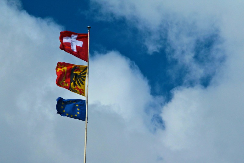"Incongruous • The flags of the Swiss Confederation, the Canton of Geneva, and the European Union. Some of my books tell me that it is principally people in this part of Switzerland which are keen for the country to become a member-state of the European Union.  As things currently stand, the Swiss have a fairly good thing going: they have negotiated individual trade and other agreements with the EU so that they can benefit from those without being encumbered with the burden of bureaucracy implicit with membership of the EU. Though of course, as I know, the <a href=""http://richardflynn.net/travel/2007/10/30/a-tale-of-swiss-bureaucracy/"" title=""A tale of Swiss bureaucracy"">Swiss are no strangers to bureaucracy</a>. One such agreement between Switzerland and the EU <a href=""http://www.forbes.com/markets/feeds/afx/2008/03/14/afx4774503.html"" title=""Switzerland to negotiate agriculture free trade agreement with EU"">was recently signed</a>."