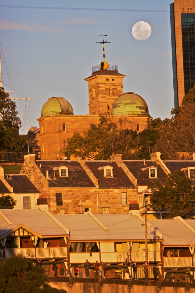 Sydney Observatory as seen from the west in the late afternoon sunlight, with  the full moon large overhead. The people standing on the street below are watching the Pope's formal arrival by boat at the Sydney World Youth Day.