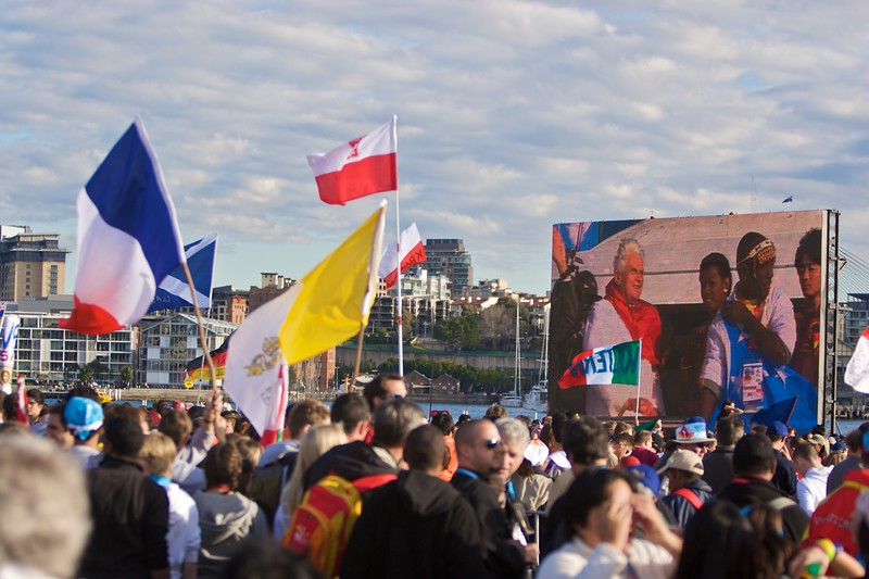 Flag-bearing pilgrims watching the Pope arrive on his boat travelling aroudn Sydney Harbour.
