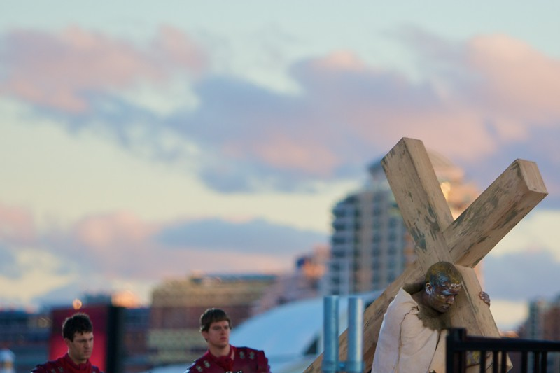 Simon of Cyrene carrying the Cross at the Stations of the Cross for the World Youth Day in Sydney, followed by a couple of Roman soldiers.