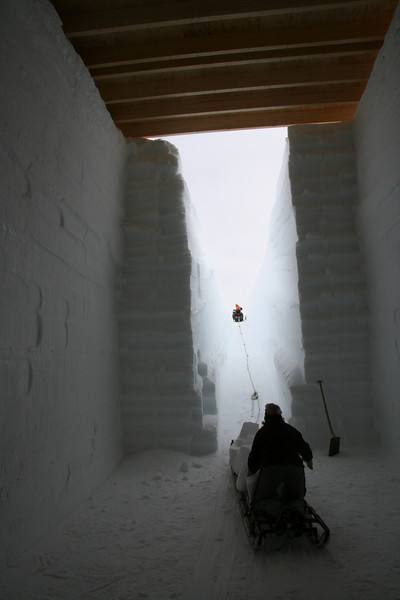 Blocks of snow are dragged out of drill trench.<br /> <br /> Sneblokke trækkes ud af borehallen.<br /> Photo: Dorthe Dahl-Jensen