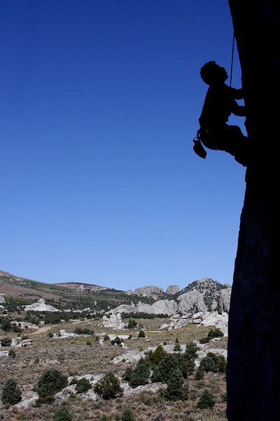 City of Rocks, Idaho sits under the bright sun with Kelsey silhouetted sharply on <i>Electric Avenue 5.12</i>.