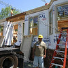 Habitat partner family member Alejandro Perez stands in front of 208 & 210 Dubois Street in the City of Newburgh on day 1 of construction