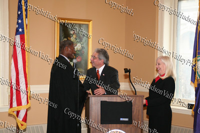 Judge B Harold Ramsey shakes Nicholas Valenine hand after swearing in Sue to right