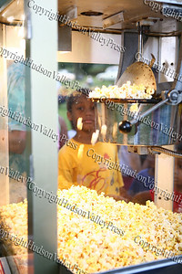 "A child watches the pop corn pop prior to the City of Newburgh Youth Bureau presenting the ""Bee Movie"" in Downing Park on Tuesday, July 29, 2008."