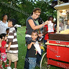 "Two-year-old Aarysa Moore is accompanied by her mother Cynthia Martinez to get some pop corn as the City of Newburgh Youth Bureau presented the ""Bee Movie"" in Downing Park on Tuesday, July 29, 2008."