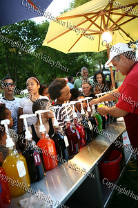 """Children line up for the many flavors of sno cones prior to City of Newburgh Youth Bureau presenting the """"Bee Movie"""" in Downing Park on Tuesday, July 29, 2008."""