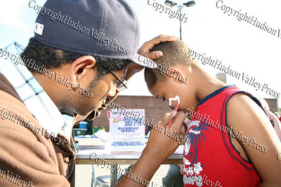 David Lewis III paints five-year-old Elijah Mason's face at the Local Awareness and Development booth during Newburgh's National Night Out.