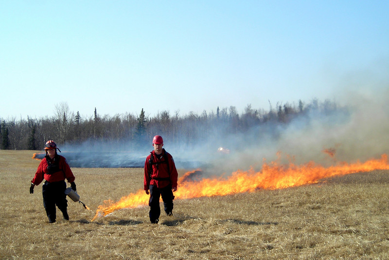 Lieutenant Tara Mellon and firing boss Jake Boothby approach across the field, leaving a trail of blazing inferno behind them.