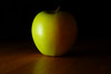 Day 211 - Bashful Fruit<br /> <br /> A yellow-green apple showing signs of blushing red<br /> <br /> <br /> The setup was a black board in back, white board on left, bounced the flash upward at a 45, and then used my hand to cover the on-camera flash which gave a rose-tint to right of the apple.  I like learning how light can be cast and the subtle differences a degree or two make. <br /> <br /> <br /> Sept 16 2008