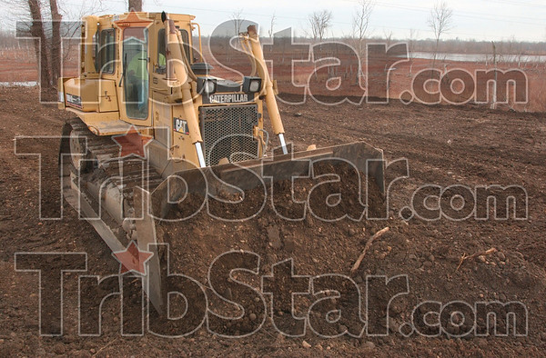 IImprovements: Gary Henderson of Feutz Construction levels fill material at the site of what will be the visitors center at the wetlands just east of West Terre Haute.