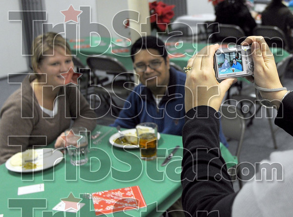 Picture this: Tiffany Macke takes a photograph of Jessica and Wes Agustine during the second annual Community Christmas Dinner at the Marshall First United Methodist Church.