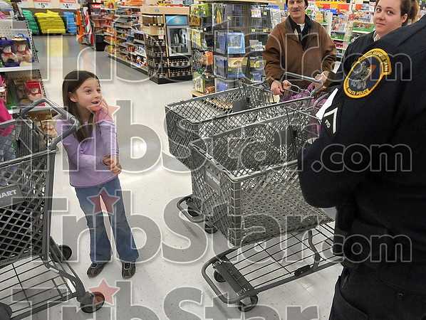 How much?!: Seven-year-old Sierra Smith reacts after Terre Haute Police Patrolman Pete Horstman, right, told her stepmother, April Hires, how much she can spend during the Shop with a Cop Program Sunday at the southside Walmart.