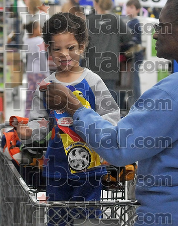 Yessss!: Malekhi Coons, 4, does some fist pumping as his grandmother, Patricia Liston, shows him one of his much sought after toys Sunday during the Shop with a Cop program at the southside Walmart.