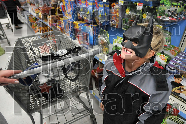 The big smile behind the mask: Six-year-old Jeremy Lee can't help but smile as he shows off his newfound Batman mask to his mom, Misty Kirkendall, during the Shop with a Cop Program Sunday morning at the southside Walmart.