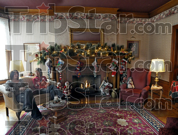 Tourists: Alana Burke and Christ Strain enjoy a holiday drink as they sit by the fire in the living room of the Farrington Bed and Breakfast Sunday afternoon as part of the Holiday Home Tour.