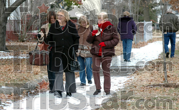 Bundled: Tourists bundle up against the cold as they walk along south seventh street enroute to several homes on the Holiday Home Tour Sunday afternoon.