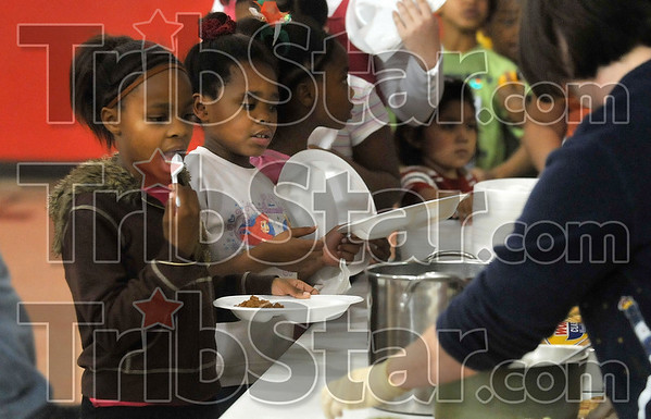 What's for dinner?: Celeste Rose and Trinity Montgomery wait with other youngsters for dinner to be served Friday at the 14th and Chestnut Community Center's Grumbling Tummies Cafe. The center received a check for $5,550 Friday from Fuqua Elementary School.