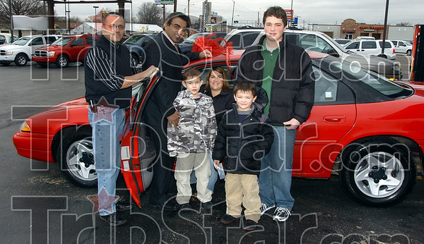 Merry Christmas: Michele Howell sits in her new car at the Car Depot dealership on South 3rd street. The car was donated by R.C. Sayyah, second from left. Aiding in the gift was Cross Tabernacle pastor Keith Taylor, left. With them are Howell's three sons, Caleb and Joshua Howell and Nick Spencer.
