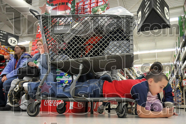 Resting after shopping (sort of): Eight-year-old Eric Westerberg finds a spot under a cart to relax in during the  74th Annual Noon OptimistÕs ÒClothe-A-ChildÓ program at the southside WalMart Saturday.