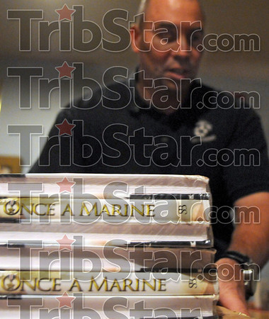 Once a Marine: Nick Popaditch place some copies of his book onto a table at the Marine Corps League Saturday evening.