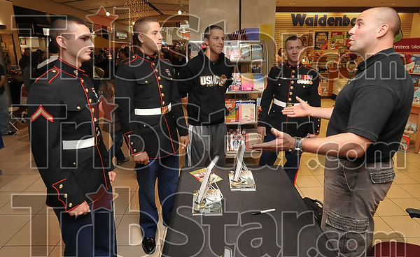 The voice of experience: Retired Marine Corps Tank Commander Nick Popaditch, right, talks with USMC Pfc. Charlie McLean, Pvt. Nick Voll, Pfc. Kenneth Wagner and SSgt. Daniel Polk during Popaditch's book signing Saturday at the Honey Creek Mall.