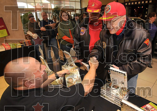 Once a Marine, always...: Former Marine Ray Kemp shakes hands with fellow Marine Corps veteran Nick Popaditch during Popaditch's book signing Saturday in Waldenbooks at the Honey Creek Mall.