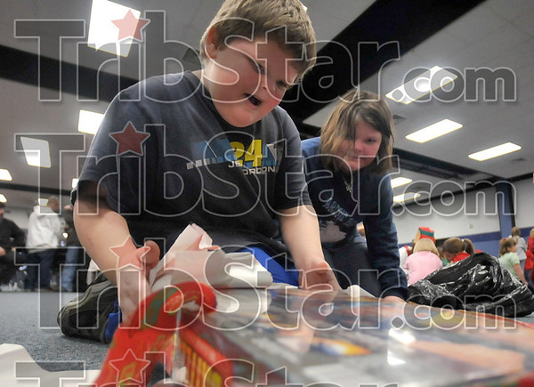 """My favorite!: Eight-year-old Gunner Smith reacts after he found the game, """"Battleship,"""" under wrapping paper during the West Vigo High School Ambassadors' Christmas Crusade Saturday at West Vigo Middle School. Looking on is  Gunner's older sister, Mikaila, 10."""