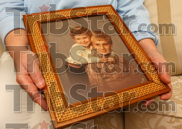 LOst chilrhood: Janet Treash hold an old photo of her sons  Garrett and Shane Mustard.