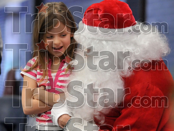Yes, I have been good!: Eight-year-old Arrin Johnson converses with Santa Claus (a.k.a. West Vigo High School biology teacher Ron Helms) during the West Vigo High School Ambassadors' Christmas Crusade Saturday in the West Vigo Middle School.
