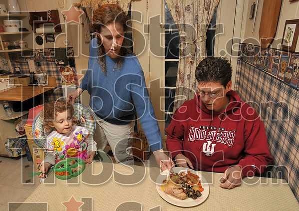 Healthy and home-cooked: Emily Tedrow gives a hot Cornish hen platter to partner, Barbara Tedrow, as daughter, Courtney, 3, looks on at the Tedrows' home Monday near Rosedale. Emily cooks healthy meals for the family which also helps Barbara lose weight.