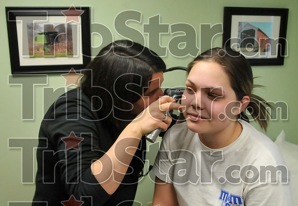 Farming background: Paris, Ill., native Dr. Denise Pine Mattas inspects the ear of patient Megan Wallace, 18, during Wallace's visit Thursday to the Cork Medical Center in Marhsall, Ill. Dr. Pine Mattas came from a rural farm family in Edgar County and decided to serve the rural Illinois community as a family practice physician.